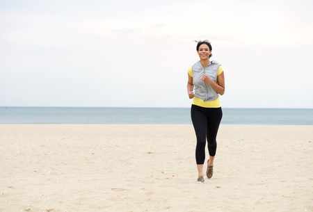 outdoor training: Full body portrait of a smiling woman running on the beach Stock Photo