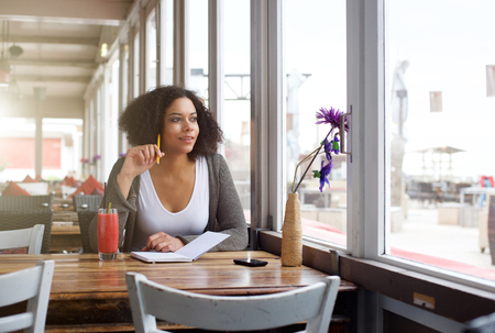 Portrait of a female college student sitting at cafe looking out of window daydreaming Imagens