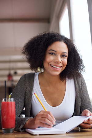 woman in black: Close up portrait of a smiling african american female student writing in book Stock Photo