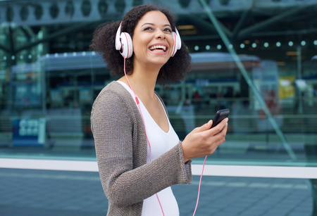pretty black woman: Close up portrait of a smiling african american woman listening to music on headphones