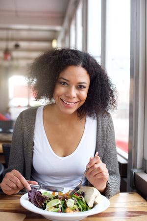 Portret van een lachende zwarte vrouw salade eten in het restaurant Stockfoto