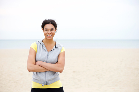 pretty black woman: Portrait of a confident african american sports woman smiling by the beach
