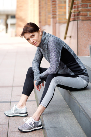 tracksuit: Portrait of an older woman resting outside after workout