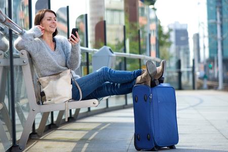 стиль жизни: Портрет старшего женщина путешествия расслабляющий с сумкой и улыбка на мобильном телефоне