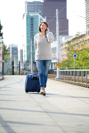 city people: Full body portrait of a travel woman walking with suitcase and mobile phone at outdoor station