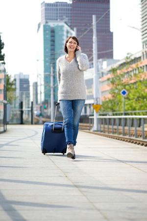 personas hablando: Retrato de cuerpo entero de una mujer caminando con la maleta de viaje y el tel�fono m�vil en la estaci�n al aire libre Foto de archivo