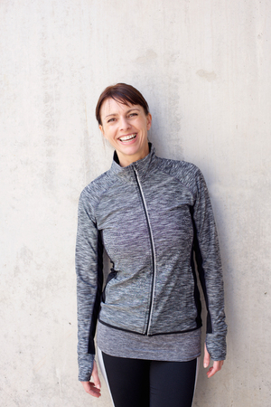 tracksuit: Portrait of a cheerful older sports woman smiling against light background