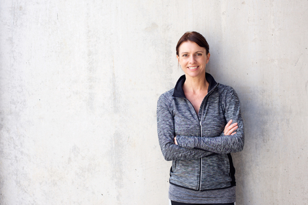 Portrait of an attractive older sports woman smiling against white wall Stock Photo