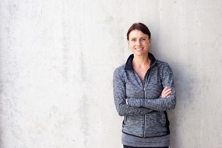 Portret van een aantrekkelijke oudere sportieve vrouw lachend tegen witte muur