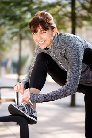 woman relax: Portrait of a smiling sporty woman tying shoelace outside