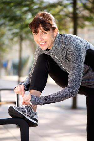 sport woman: Portrait of a smiling sporty woman tying shoelace outside