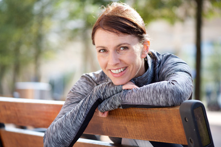 Portret van een glimlachende sportieve vrouw die buiten op de bank