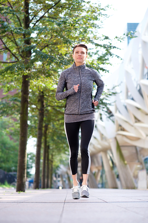 woman full body: One healthy woman running outdoors in the city Stock Photo