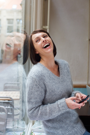 woman sweater: Side portrait woman laughing with cellphone at home Stock Photo