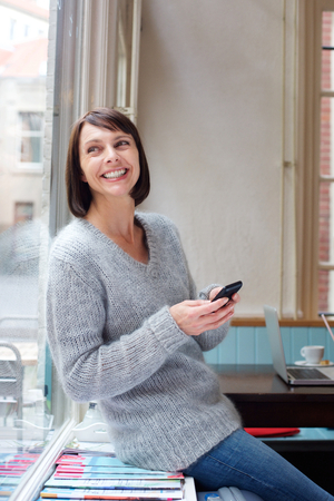 aged: Side portrait smiling woman leaning against window using mobile phone Stock Photo