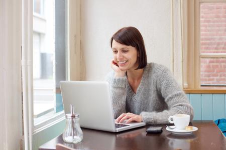 Portret van een glimlachende vrouw zit bij koffie met laptop Stockfoto