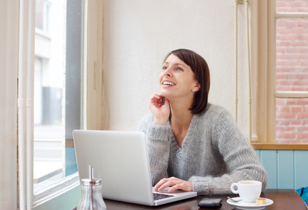 laptop home: Portrait smiling middle aged woman sitting at cafe with laptop