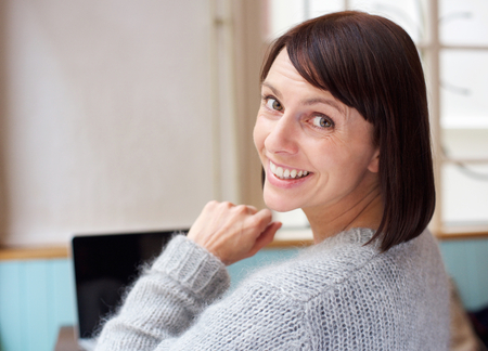 behind: Behind portrait woman smiling at home with laptop Stock Photo