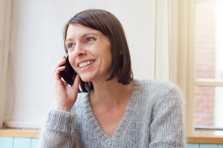Close up portrait attractive woman smiling with mobile phone at home Stock Photo