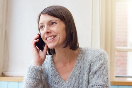 Close-up portret aantrekkelijke vrouw die lacht met de mobiele telefoon thuis Stockfoto