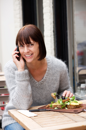 aged: Portrait of a woman eating and smiling with mobile phone Stock Photo