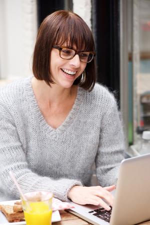 person sitting: Retrato de una mujer sonriente con gafas usando la computadora port�til