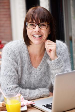 밖에 서 노트북과 함께 앉아 쾌활 한 여자의 초상화 스톡 콘텐츠