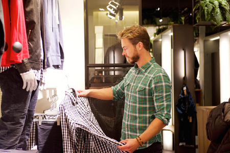 shopper: Portrait of a male shopper looking at clothes in store