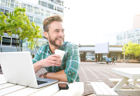 man drinking coffee: Portrait of a smiling man sitting outside with laptop and coffee