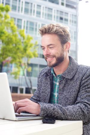 bata blanca: Retrato de un hombre sonriente que trabaja fuera con el port�til Foto de archivo