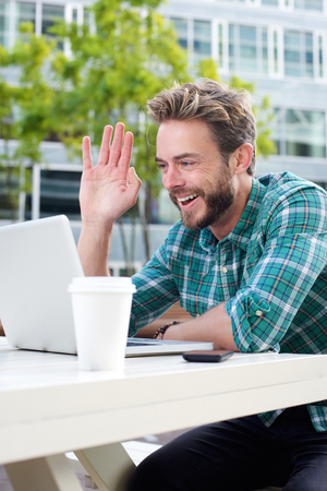 man with laptop: Portrait of a smiling man waving hello on chat with laptop