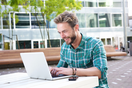 working model: Portrait of a smiling man working on laptop outdoors