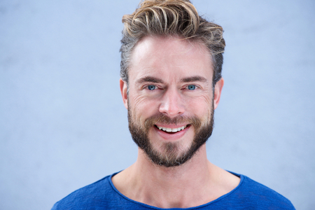 Close-up portret man met baard lachend tegen de grijze achtergrond Stockfoto