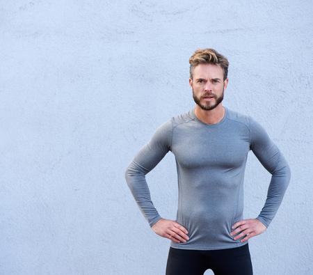 fitness men: Retrato de un entrenador f�sico grave de pie contra el fondo gris Foto de archivo
