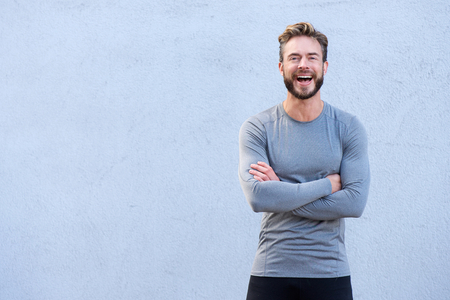 people laughing: Portrait of a male fitness trainer laughing with arms crossed
