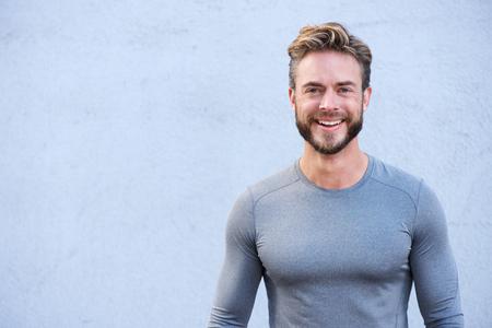 fitness men: Cerca de retrato de un entrenador deportivo sonriente sobre un fondo gris
