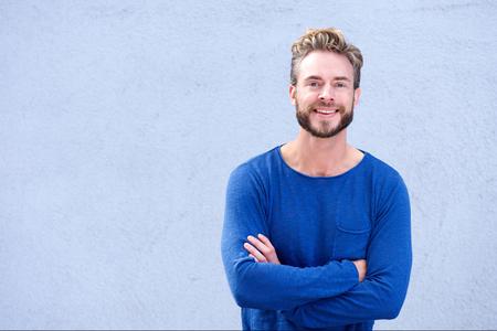 modelos hombres: Retrato de un hombre sonriente confianza con los brazos cruzados sobre fondo gris Foto de archivo
