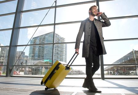 Zij portret van een glimlachende reis man lopen en praten op mobiele telefoon