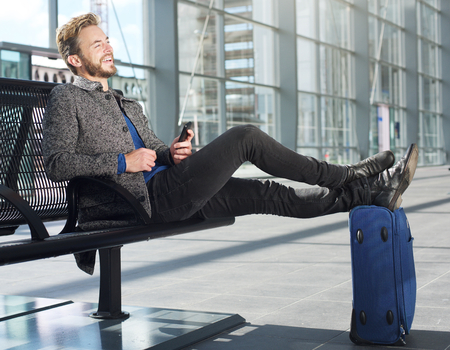 text cool: Portrait of a travel man relaxing at airport with cellphone