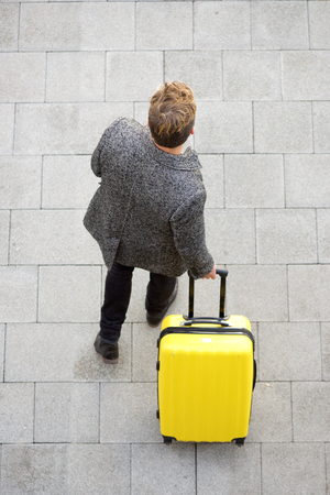 Top view traveling man walking with suitcase Stock Photo