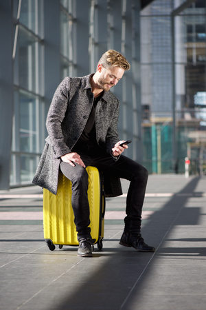 cool guy: Portrait of a cool travel guy sitting on suitcase looking at mobile phone