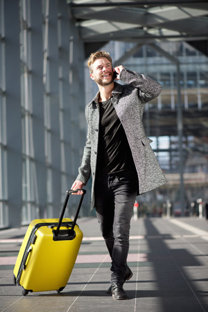 Full length portrait smiling travel man walking with cell phone and suitcase