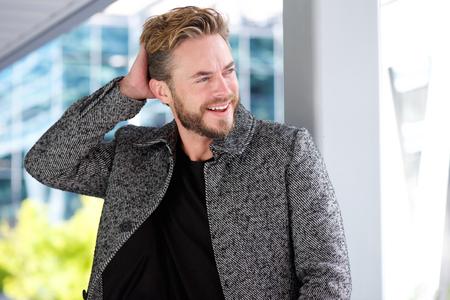 modelos hombres: Close up retrato de un hombre guapo sonriente con la mano en el pelo