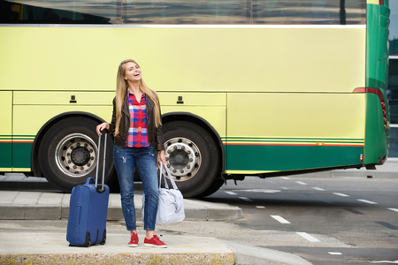 baggage: Portrait of a smiling travel woman standing outside at bus terminal with bags