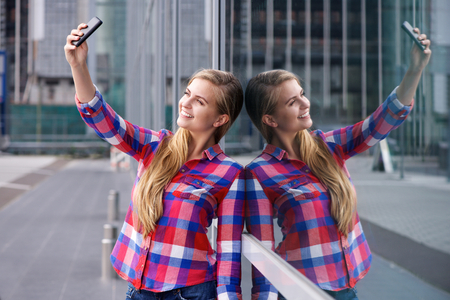 reflection: Portrait of a smiling young woman taking selfie with reflection Stock Photo
