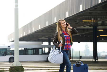 carry: Portrait of a young woman smiling with travel bags and mobile phone