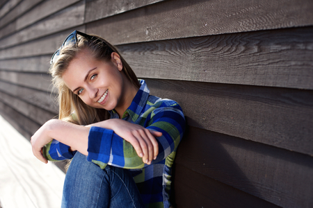 young woman smiling: Portrait of a smiling young beautiful woman sitting outside
