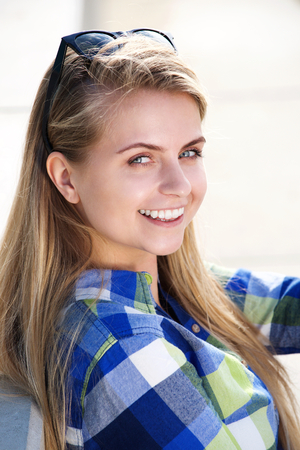 Close up portrait of a smiling young blond woman sitting outside