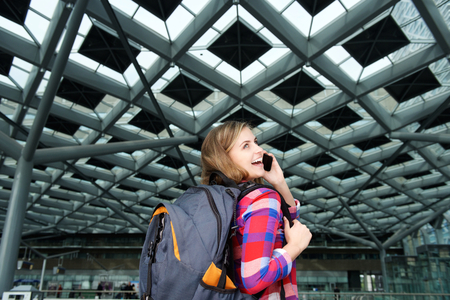backpacks: Portrait of a smiling young travel woman with backpack and mobile phone Stock Photo