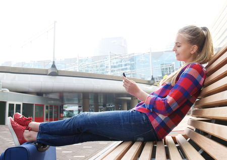 airport terminal: Side portrait of a smiling travel woman sitting outside looking at mobile phone Stock Photo